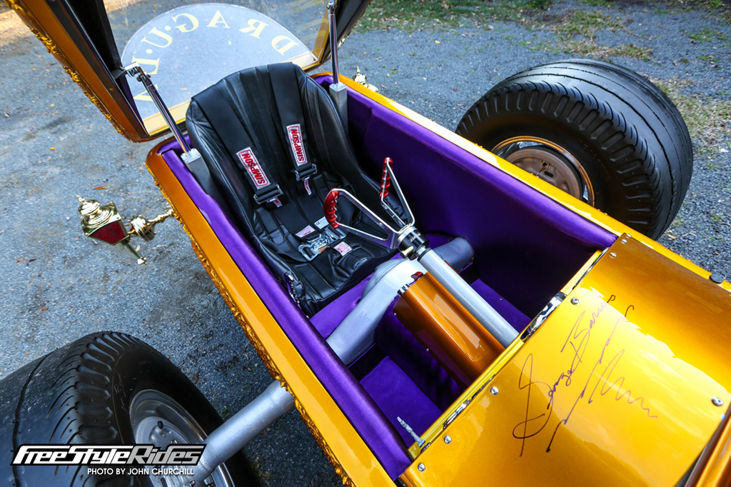 David sits in a vintage Kirkey bucket and grips an era-correct butterfly wheel as used in many 60s dragsters